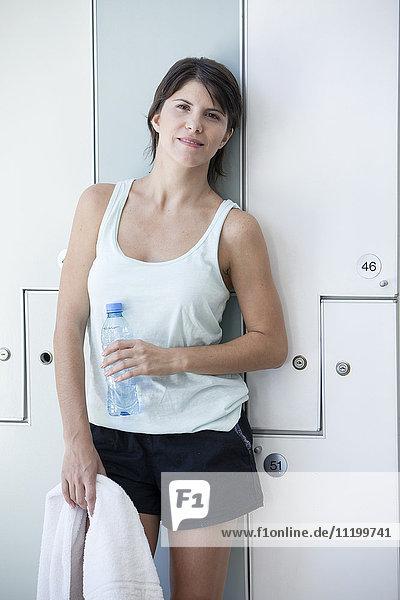 Frau entspannt sich im Umkleideraum mit Wasserflasche  Portrait