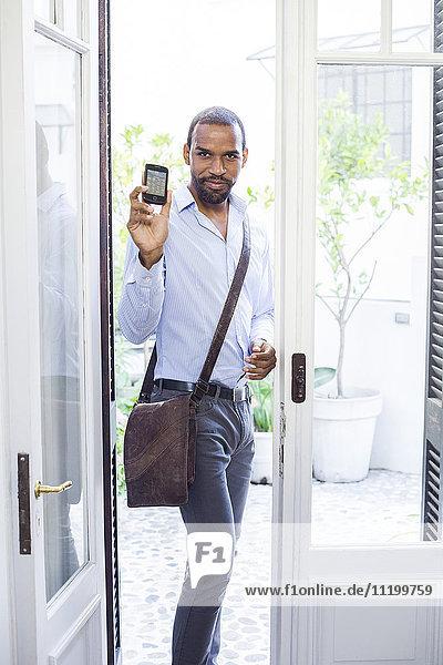 Mann steht in offener Tür  zeigt Smartphone und lächelt