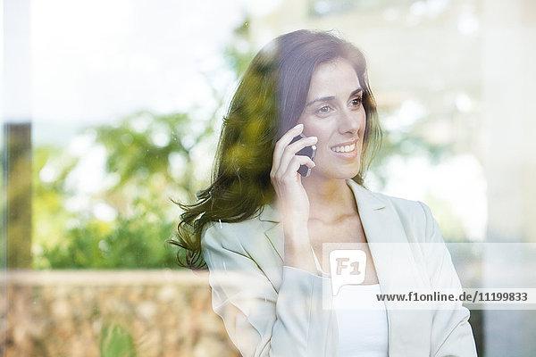 Geschäftsfrau schaut aus dem Fenster  während sie mit dem Handy telefoniert.