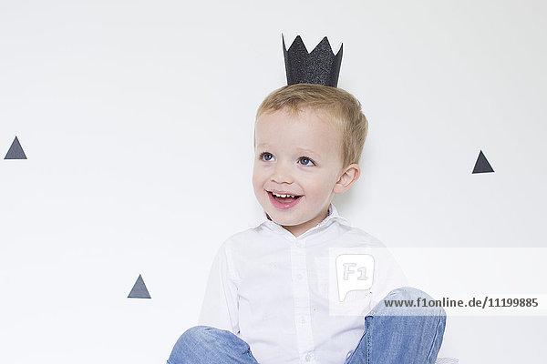 Kleiner Junge mit Papierkrone
