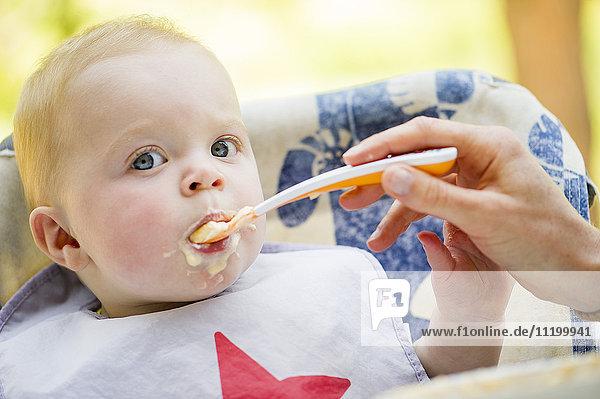 Baby wird mit Löffel gefüttert