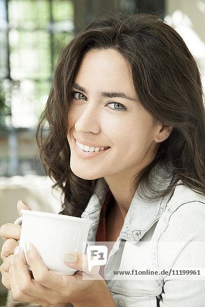 Junge Frau genießt eine Tasse Kaffee im Freien