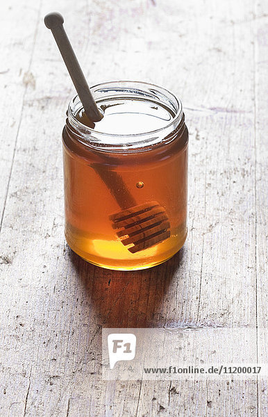 Dipper stick with honey in glass jar on wooden table