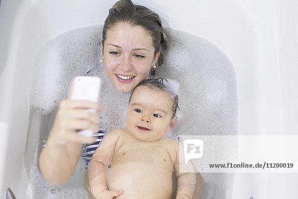 Mutter fotografiert sich und ihr Baby beim Baden mit dem Smartphone.