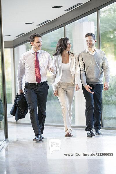 Geschäftsleute gehen gemeinsam durchs Büro