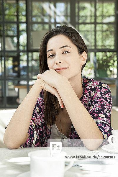 Junge Frau am Frühstückstisch im Freien