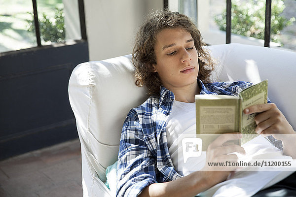Young man reading book on couch
