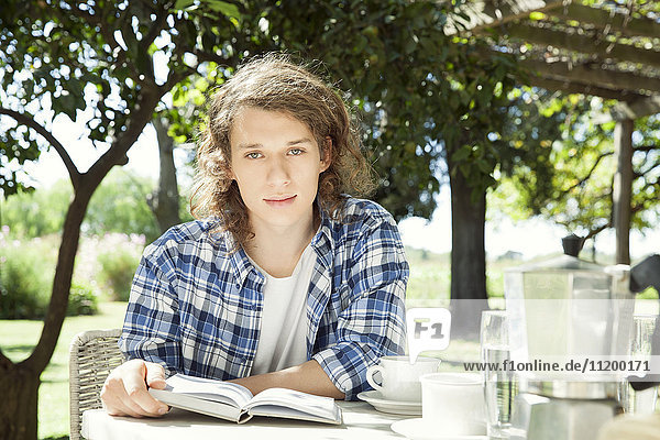 Junger Mann am Frühstückstisch im Freien mit Buch