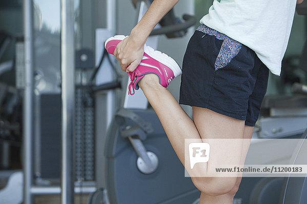 Frau streckt sich im Fitnessstudio  abgeschnitten