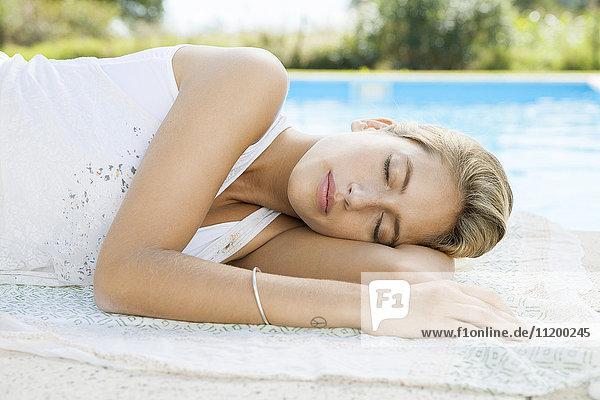 Frau ruht am Pool mit geschlossenen Augen