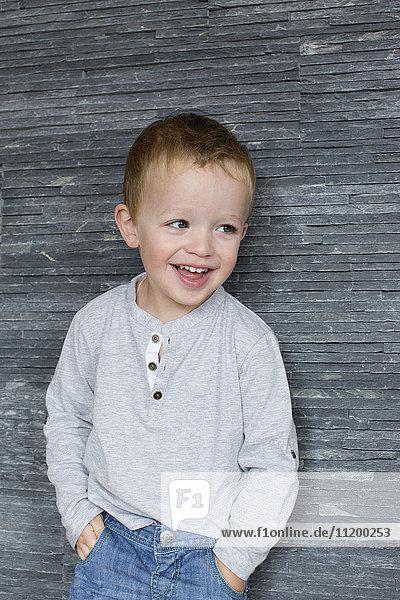 Kleiner Junge lehnt sich mit den Händen in den Taschen an die Wand und lächelt fröhlich.