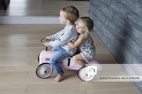 Junge Geschwister  die zusammen auf einem Spielzeugauto fahren
