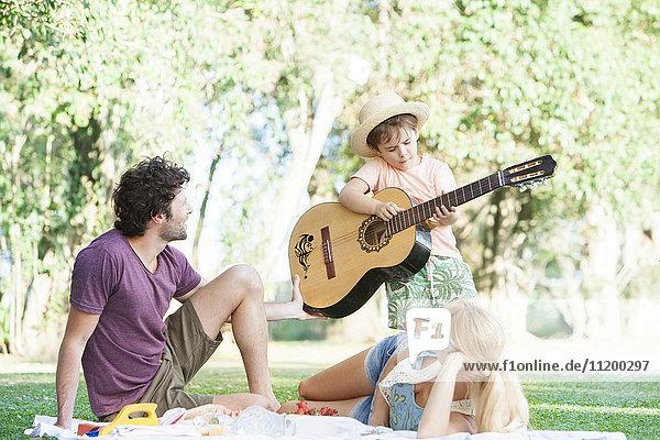 Eltern  die dem Sohn das Gitarrenspiel beibringen.