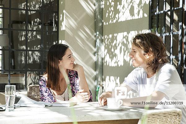 Junges Paar beim Plaudern am Frühstückstisch im Freien
