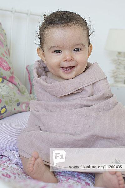 Baby im Handtuch gewickelt  lächelnd  Portrait