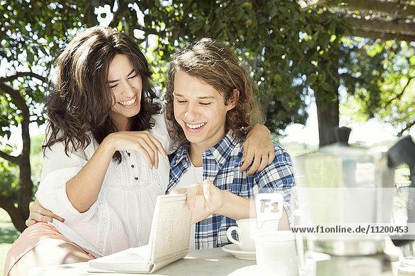 Junges Paar diskutiert Buch am Frühstückstisch im Freien