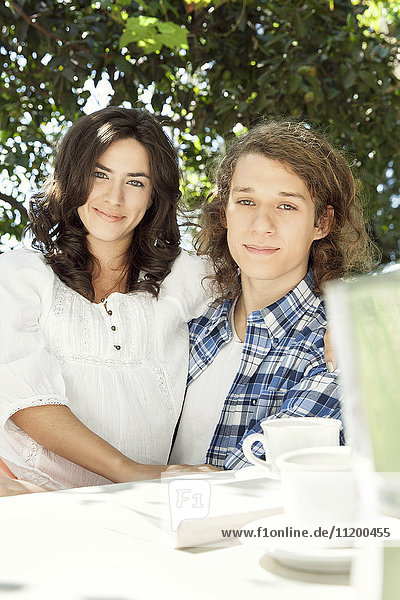 Young couple at breakfast table outdoors