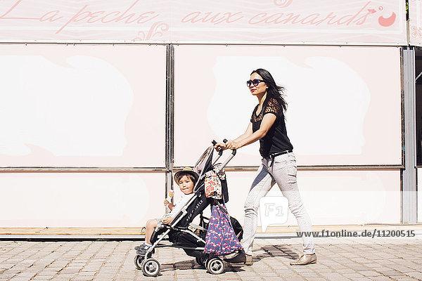 Mutter schiebt Kleinkind Sohn im Kinderwagen auf dem Bürgersteig