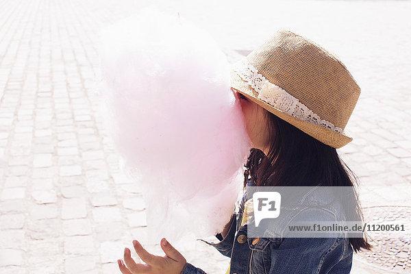 Kleines Mädchen vergräbt ihr Gesicht in Zuckerwatte Kleines Mädchen vergräbt ihr Gesicht in Zuckerwatte