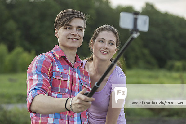 Smiling young couple taking selfie through monopod at park against trees