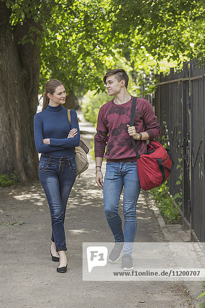 Full length of couple walking on sidewalk by fence against tree