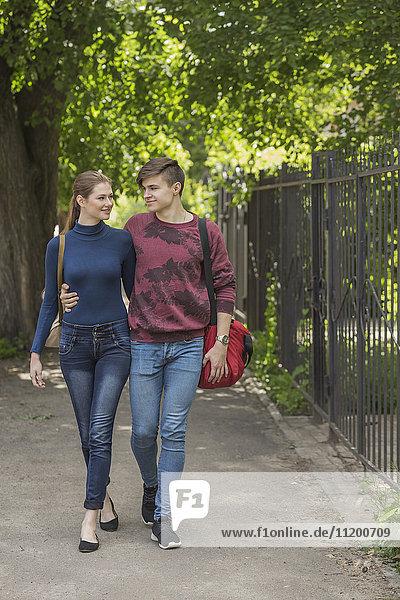 Full length of loving couple walking on sidewalk by fence