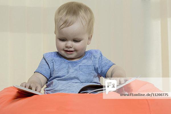 Nahaufnahme des süßen  lächelnden Mädchens beim Lesen eines Buches  während es zu Hause auf einem Bohnensack sitzt.