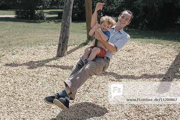 Fröhlicher Vater schwingt mit Sohn auf dem Spielplatz