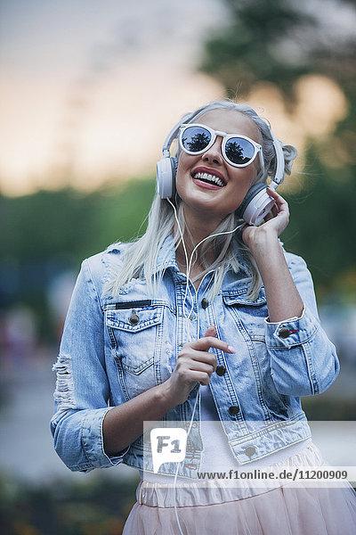 Fröhliche modische Frau mit Sonnenbrille beim Musikhören über Kopfhörer