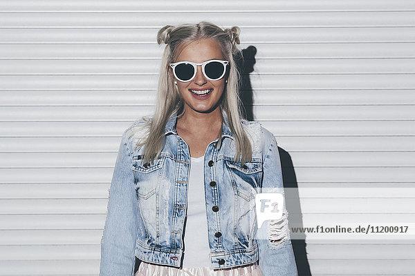 Porträt einer modischen jungen Frau mit Sonnenbrille gegen den Fensterladen