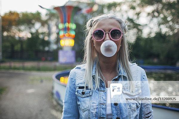 Portrait einer jungen Frau mit Sonnenbrille beim Blasen von Kaugummi im Vergnügungspark
