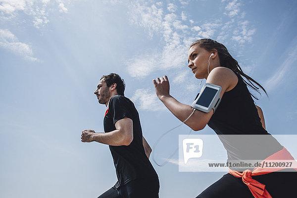 Niederwinkelansicht eines jungen Mannes und einer jungen Frau beim Joggen gegen den Himmel