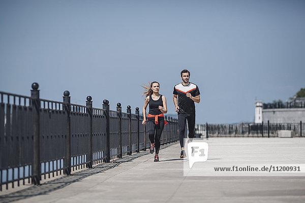 Gesamtansicht von Freunden  die auf der Promenade gegen den klaren Himmel laufen.