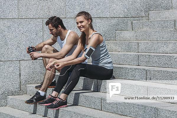 Glückliche Freunde in Sportbekleidung sitzen auf Stufen an der Wand