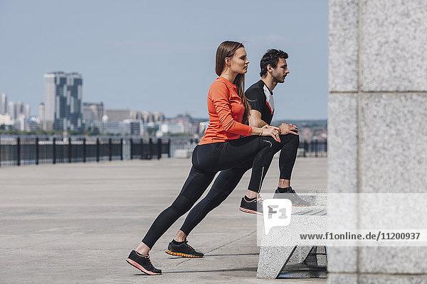 Seitenansicht der entschlossenen Freunde  die während des Trainings auf der Promenade die Beine strecken.