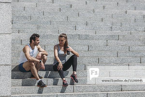 Freunde  die nach dem Training auf der Treppe sitzen und sich unterhalten