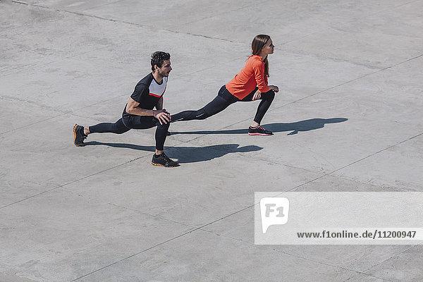 Hochwinkelansicht von Personen  die bei Sonnenschein die Beine auf dem öffentlichen Platz strecken.