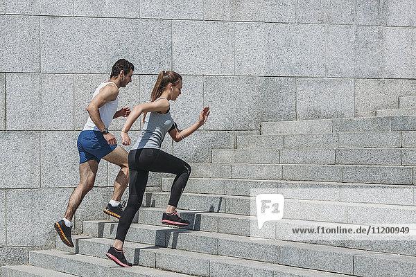 Entschlossene Freunde joggen Schritt für Schritt durch die Wand