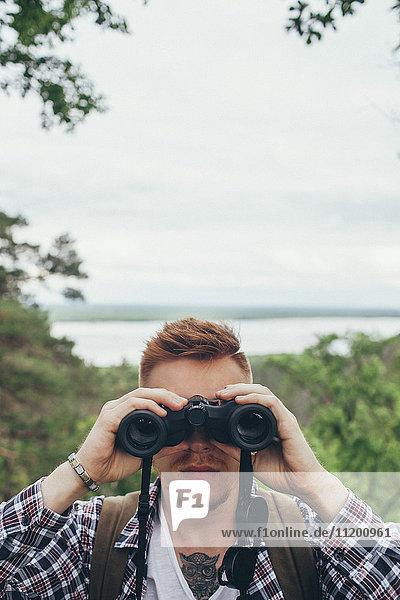 Nahaufnahme eines jungen Mannes mit Fernglas beim Wandern im Wald gegen den Himmel