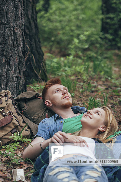 Romantisches Paar auf dem Feld im Wald liegend