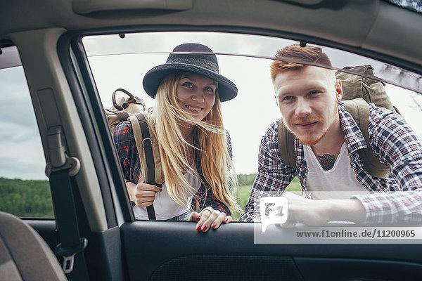 Lächelnde männliche und weibliche Rucksacktouristen schauen in die Autoscheibe