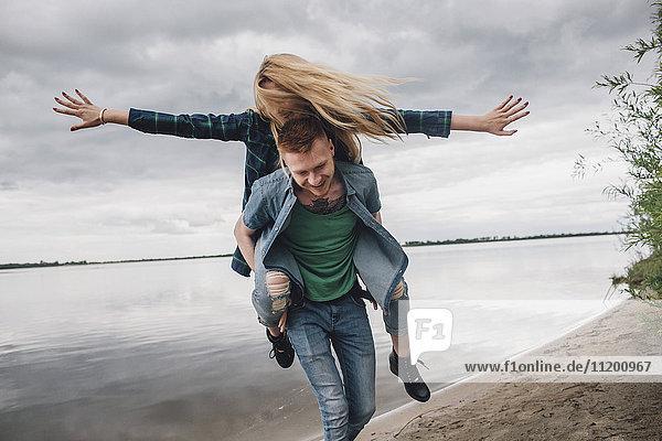 Glücklicher Mann Huckepack-Freundin am Seeufer gegen Himmel