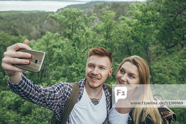 Lächelndes Paar nimmt Selfie durch Smartphone im Wald mit