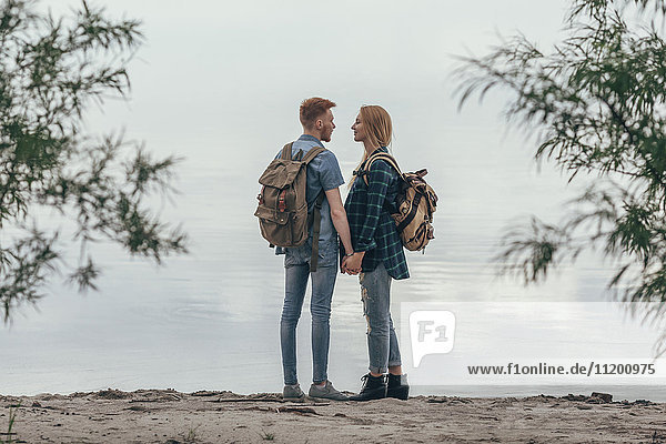 Paar hält sich an den Händen  während es am Seeufer steht
