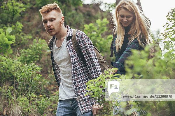 Junges Paar beim Wandern inmitten von Pflanzen im Wald