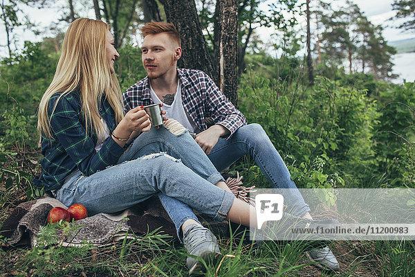 Mann schaut Freundin an  die eine Tasse hält  während sie sich unter einem Baum im Wald ausruht.