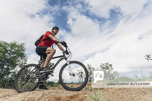 Tiefblick auf den Mann beim Mountainbikefahren in ländlicher Umgebung gegen den Himmel