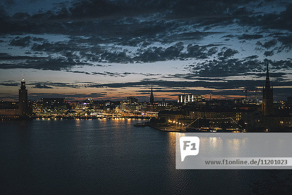 Scenic view of waterfront and illuminated city against sky at dusk  Stockholm  Sweden