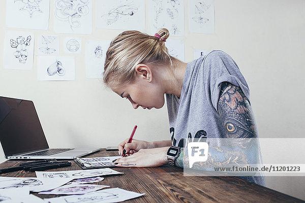 Sicherer Tätowierer bei der Arbeit am Laptop im Kunstatelier