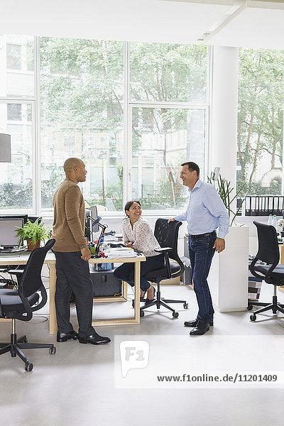 Glückliche Geschäftsleute  die mit einer Kollegin im Kreativbüro kommunizieren.